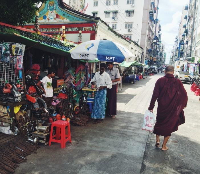 Monk and shop in downtown Yangon, Myanmar
